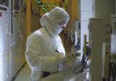Fotograma presentación en YouTube de la tecnologia de 14 nanómetros de Intel. Científico toma apuntes mientras observa un sistema.