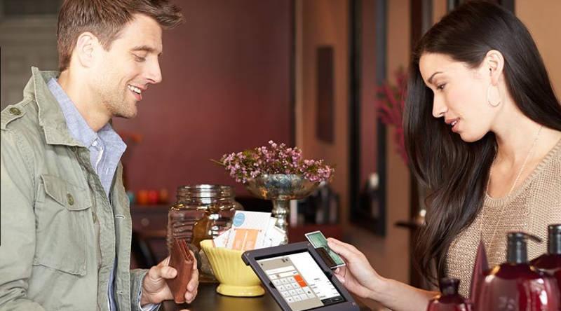 Mujer con el lector de tarjetas de Amazon procesa la compra de un cliente varón.