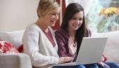 Dos mujeres, una adulta y una adolescente, miran sonrientes la pantalla de un laptop.