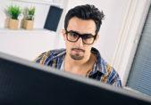 Joven con gafas frente a pantalla de PC