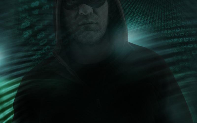 Silueta de ciberdelincuente con código binario de fondo