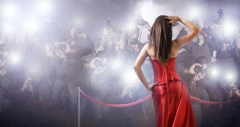Concepto: Famosa de espaldas es fotografiada por una multitud de personas.