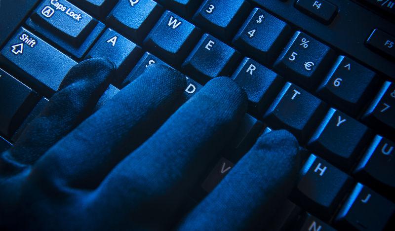 Guante negro sobre teclado cibercrimen
