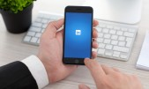 Ejecutivo sostiene smartphone en cuya pantalla se ve el logotipo de LinkedIn