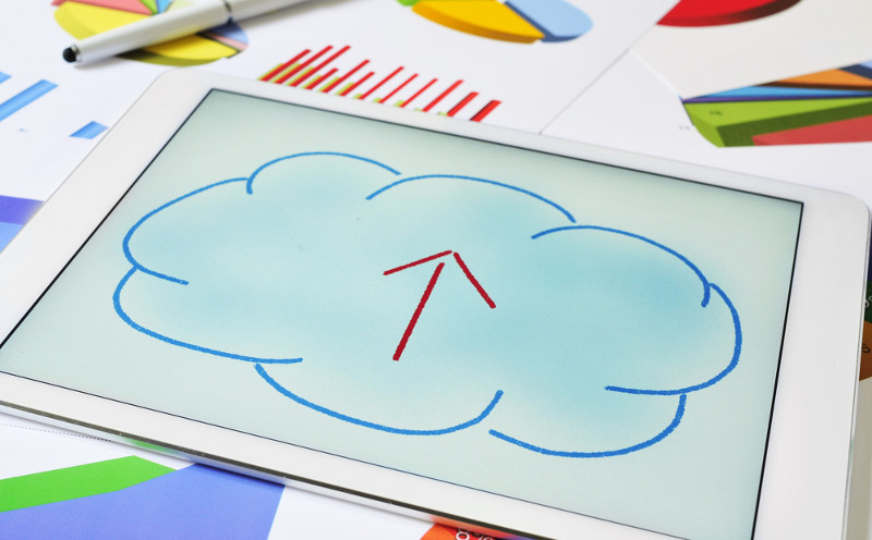 Dibujo de una nube con flecha en su interior, sobre la pantalla de una tableta, ilustrando el concepto de subir contenidos a la nube