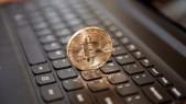 Moneda Bitcoin física sobre teclado negro