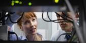 Dos técnicos, hombre y mujer, en centro de datos