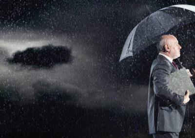 Hombre de negocios con paraguas en la lluvia