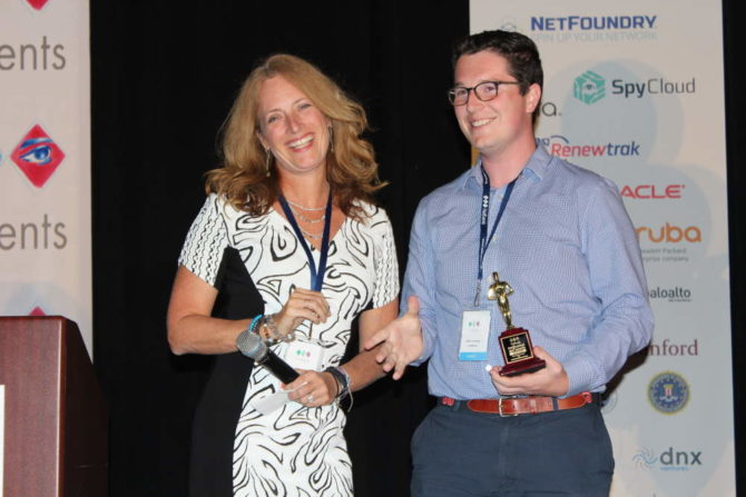Erin Dunne, Director of Research Services, Vertical Systems Group, entrega el premio a Ethan Tashman, Darktrace
